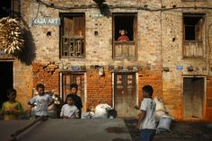Oct. 8, 2012. A girl looks out from the window of her home as children play ping-pong outside in the ancient Nepalese city of Bhaktapur.