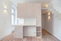 Spamroom est à l'origine de ce micro-appartement. Les architectes ont d'abord détruit toutes les cloisons pour partir d'une surface neutre et rectangulaire. L'élément principal de l'appartement est ce module en bois qui trône au milieu et qui sert de rangements, cuisine, bureau et toilettes. Un escalier minimaliste en métal blanc dessert la zone de couchage. Le design est minimaliste et contemporain avec l'utilisation massive de couleurs et de matières claires pour agrandir l'espace.