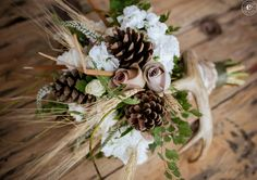 Bridal bouquet for a rustic fall wedding, made with flowers, cattails, wheat, pine cones and a deer antler. Flowers by Viviano Flower Shop, photo by The People Picture Company.