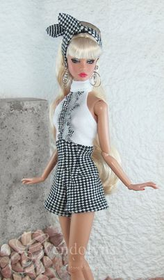 Breezy retro summer romper for your 12 Beach Beauties!  Poppy stays cool and cute in a two tone knit and cotton gingham jumpsuit with high waisted pleated shorts and ruffled halter top. Coordinating hair tie completes the look.  Snap back closure.  Doll is not included.