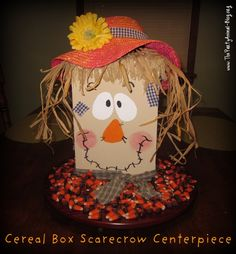Super easy Cereal Box Scarecrow Centerpiece. Depending on the box, may just turn inside out instead of paint the face color for a more rustic look.  I wouldn't use cereal. I'd just use more raffia or straw.
