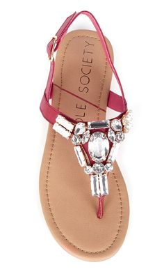 Coral flat sandals bejeweled in sparkling crystal stones along the t-straps. Perfect for spring & summer.