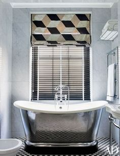A bath features a polished-iron tub by the Water Monopoly; the tub fittings and towel racks are by Lefroy Brooks, the towels are by Ralph Lauren Home, and the Roman shade is made of a Pierre Frey fabric
