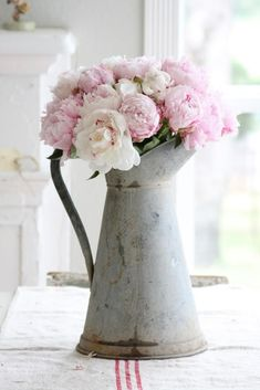 jug made from rusty metal, with curved handle, containing pale pink peonies, country cottage furniture, rough cream tablecloth, with three red stripes #countryfurniture