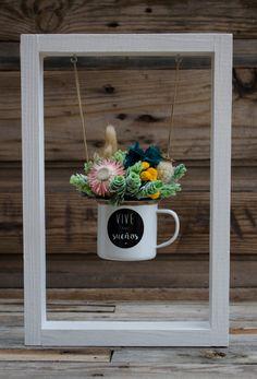 """Flores preservadas y secas en una taza con la inscripción: """"Vive tus sueños"""". Se puede colgar en la pared a modo de cuadro o ponerlo sobre una superficie."""