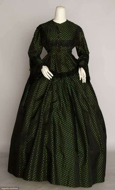 "SILK BROCADE DAY DRESS, c. 1860  2-piece green & black small sprigged brocade, peplum bodice, black lace trim, B 36"", W 22.5"", Skirt L 41""-45"", excellent."