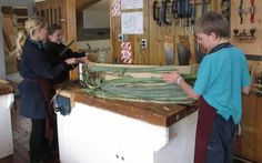 Nests: students weaving flax onto the cardboard frame