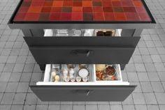 Cucina vintage ad isola, in acciaio nero. Oltre a lavastoviglie, congelatore, forno e contenitori per la raccolta differenziata, i cassettoni possono contenere anche frigoriferi e congelatori.