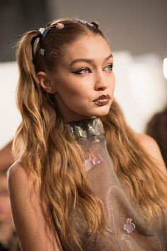 Gigi Hadid in the SS17 Fendi show at Milan Fashion Week, modelling major cat-eye liner, metallic glitter lipstick and cute pigtails with hair adornments