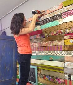 DIY wood pallet wall made of various stained and/or decoupaged pallet pieces