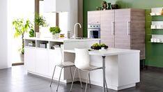 Un îlot central dans une cuisine ouverte délimite le salon et offre un aménagement complet et compact