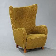 Mogens Lassen, attributed: High back winged armchair with legs of elm. Sides, back and seat upholstered with yellow wool.
