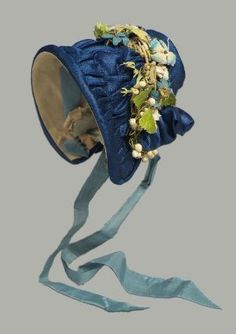 French about 1840  6.5 cm (2 9/16 in.)  Doll's bonnet of dark blue satin faced with yellow taffeta with light blue ribbon ties, trimmed on top with wreath of artificial flowers, dark blue velvet ribbon, and blonde lace.