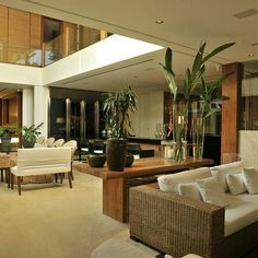 Sala de estar integrada ao jantar, com mesas em madeira, pé direito duplo e sofá.