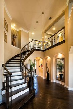 The smart use of lighting helps to make sure your eyes are where they need to be when you enter this luxury foyer. #Foyerdecorating Dream House Interior, Interior Stairs, Dream Home Design, Home Interior Design, House Design, Curved Staircase, Staircase Design, Foyer Decorating, Interior Decorating