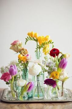 Small vases with individual dainty fresh flowers. Centerpiece.