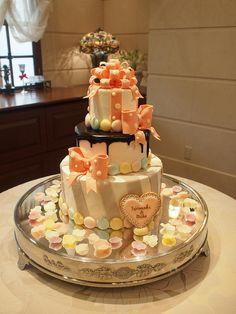 マカロンいっぱいのキュートなケーキです。 大きなリボンはチョコレート。 カラフルな3段ケーキです。