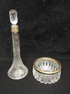VINTAGE RUSSIAN CUT GLASS DECANTER AND CANDY OR NUT BOWL WITH SILVER REPOUSSE RIM. BEARS HALLMARKS THAT INDICATE THEY HAVE 875/1000 SILVER CONTENT AND WERE PRODUCED IN MOSCOW WITH A SICKLE AND HAMMER WITHIN A STAR AND THE LETTER M NEXT TO IT. 3H X 6W
