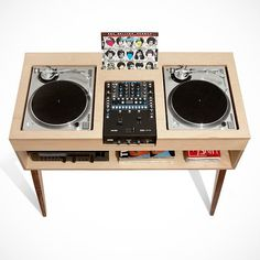 """As a companion to the Record Stand, the ATOCHA DESIGN DJ Stand gets you into music-mixing with minimalist design and maximal style. DJ furniture takes a step forward with the exciting new version of the DJ desk, the ATOCHA DESIGN DJ Stand. The DJ Stand is available in the classic """"battle-style"""" or """"non battle-style"""" positions for two turntables and mixer. The shelf allows you to conveniently store components, accessories, LPs or singles, with a pivoting bayonet for hanging your headphones…"""