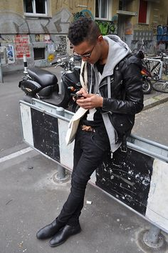 grey hoody under black leather biker jacket, black and white tshirt, black skinny jeans and shoes.  hair: shaven back and sides, let the curls out