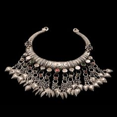 Silver Torque | Afghanistan | Circa Mid 20th Century.  Most probably designed for a bride on her wedding day (circa 1950). Each etched, plain or crystal coin carries a clutch of charmed silver hearts, contributing gentle sound and movement to the necklaces appeal. The red, green and blue stones were sourced locally.