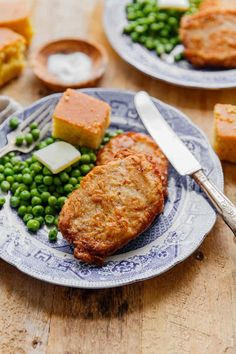 2 Southern Fried pork chops recipe on blue plate with green peas, butter and cor. - 2 Southern Fried pork chops recipe on blue plate with green peas, butter and cornbread - Southern Fried Pork Chops, Pan Fried Pork Chops, Fried Steak, Pork Rib Recipes, Meat Recipes, Dinner Recipes, Spinach Recipes, Sausage Recipes, Barbecue Pork Ribs