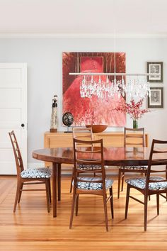 This mid-century dining room has a splash of red in the color palette. The piece of art incorporates a red tone and pairs well with the dark finish of the rosewood dining table. A crystal chandelier gives the space a little sparkle.