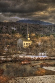 Storm clouds over de New England small town of Stowe, Vermont Community Church nestled in de center of town_ USA