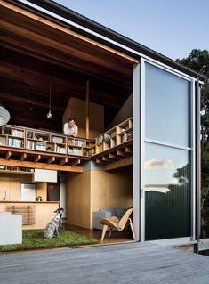 Modern small space in New Zealand with deck and lofted bedroom with shelving -- Architect: WireDog Architecture. Photo by Paul McCredie