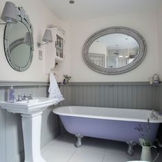 This traditional bathroom features a restored Victorian roll-top bath and panelling painted in a subtle grey.