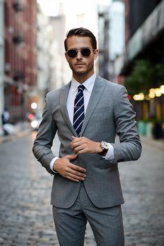Grey suit + navy striped tie + chrome tie bar + round metallic sunglasses