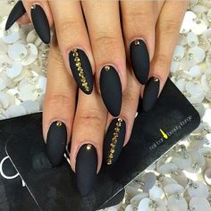 All black matte nails in stiletto or oval shape with gold studs at the base and along the centre for the accent nail #nailart...x