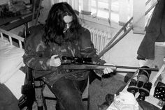 """ONE THOUSAND PINS:  A top sniper, codenamed """"Arrow,"""" loads her gun in a safe room in Sarajevo, June 30, 1992.  The former journalism student, 20 years old, said she didn't know how many people she had shot; she claimed most of her targets were other snipers on the Serbian side. Note the advanced optics she kept on her table. She was shooting a standard deer rifle with no improvements. She also kept other firepower visible just behind her chair."""