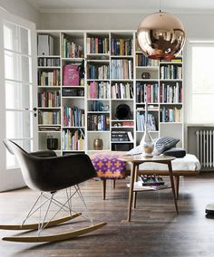 tom dixon copper shade pendant living area bookshelves Eames rocker