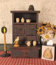 """This sweet Mini Stepback Cupboard features five working drawers and two surfaces for displaying your favorite miniature collectibles. Aged Black over Red finish. 12½""""w by 19½"""" h by 9""""d.  $165"""