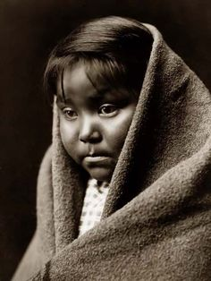 """1904 Edward S. Curtis photograph of an Indian Child named """"Child of the Desert"""". The photo is a Head-and-shoulders portrait of a Navajo Indian child, facing front, blanket around back of head and shoulders."""