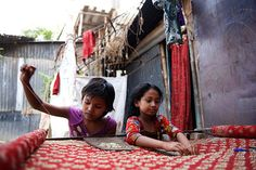 Shilpi, 10 (left) and a friend embellish a luxury saree with beads in Dhaka, Bangladesh. Shilpi attends a local UNICEF-supported school in addition to spending three to four hours each day on embroidering, helping to ease the workload of her mother, who struggles to provide for her five children. Each of Shilpi's siblings work in an informal garment factory – also play a vital role in the family's survival. © UNICEF/Shehzad Noorani