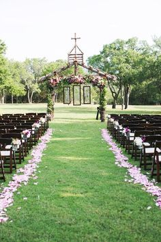 Flower petal ceremony aisle and custom-made arbor covered in flowers with stained glass | EE Photography | Wild Bunches Floral | Theknot.com