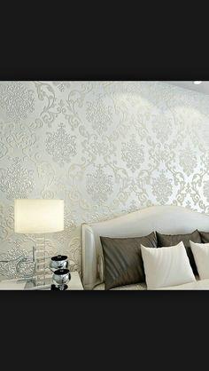 Elegant Silver foil demask wallpaper behind bed head.