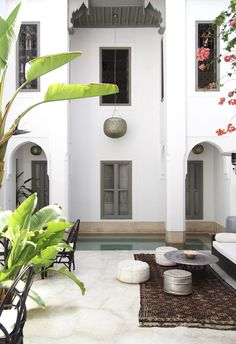Modern Arabian Exterior: Arched doorways, clean lines, plaster walls, Persian rug, low setting