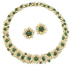 A SUITE OF EMERALD AND DIAMOND 'RÉGENCE' JEWELLERY, BY VAN CLEEF & ARPELS  Comprising a necklace designed as a series of brilliant-cut diamond flowerheads, each set with a cabochon emerald pistil, to the emerald details; and a pair of ear clips en suite, made in 1956, necklace 33.5 cm inner circumference, ear clips 2.3 cm long, with French assay mark for gold  Signed Van Cleef & Arpels, necklace no. 76143 and ear clips no. 76144
