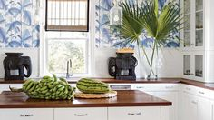 Palm-frond wallpaper in a graphic cerulean-and-white combo brings a bold punch to this island kitchen. Rich mahogany countertops and a cheeky-pair of ebony elephants ground the bold look and keep the space from feeling top heavy.