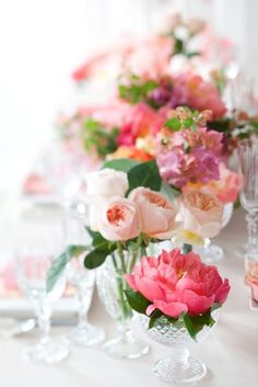 roses and peonies. For a round table, do one large, tall arrangement and then a few of these sherbert glasses with roses and peonies around them.