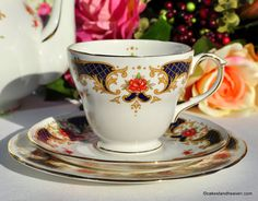 Duchess Westminster classical panels and roses pattern vintage bone china teacup, saucer and tea plate trio..  Cobalt blue panels with honey coloured scrolls, dainty red roses and gold gilding.  Teacup 8.5cm wide x 7.5cm tall. 14cm Saucer. 16.5cm Tea Plate.  Duchess China made by A. T. Finney and Sons Ltd., Duchess China Works, Longton, Staffordshire Potteries, England.  In excellent condition.