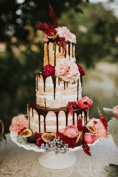 flower topped naked wedding cake with chocolate drizzle