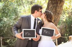 bride and groom with cute mr and mrs chalkboard signs