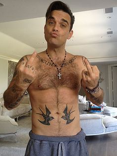 Robbie Williams showing off his tattoos