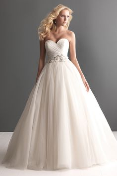 A soft and romantic tulle ball gown This design features an asymmetrically ruched strapless bodice with a sweetheart neckline and natural waistline defined with beading and floral detail
