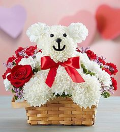 Beary Sweet™  EXCLUSIVE We've put a fresh, fun twist on the tradition of giving a teddy bear to your love! Handcrafted from fluffy white mums and crisp carnations, our cute and cuddly cub arrives in a charming handled basket filled with a striking mix of red mini carnations and pink limonium. Holding a single romantic red rose in his paw and finished off with a red satin bow, our truly original bear is a sweet way to show how much you care!
