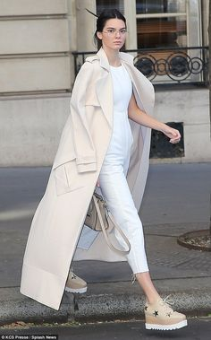 Model credentials: Kim Kardashian's younger sister looked incredible in her form-fitting white jumpsuit and chic trench coat